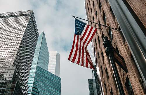 city low angle photo of flag of U.S.A architecture
