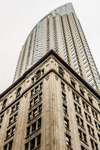 city low angle photo of high rise building under gray sky architecture