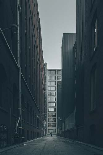 city man walking in the middle of city buildings under gray clouds grey