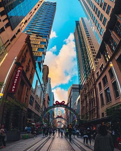 city people on street between buildings downtown
