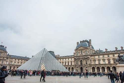 city people standing near Louvre Museum town