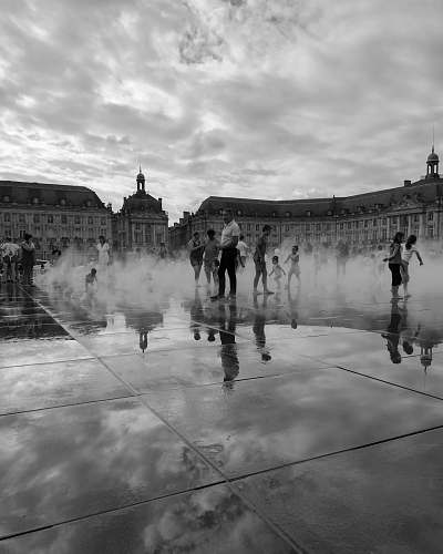 city people standing on outdoor water sprinkler park black-and-white
