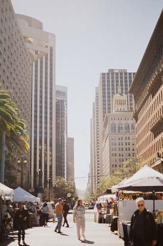 city people waking in between high rise buildings metropolis