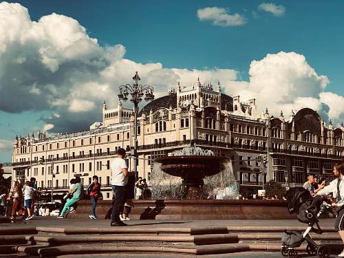 city people walking and sitting beside water fountain under cloudy sky during daytime urban