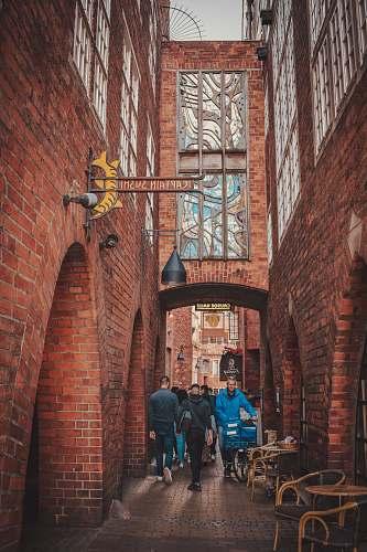 city people walking between building brick