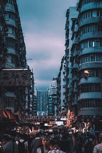 city people walking between buildings during nighttime metropolis