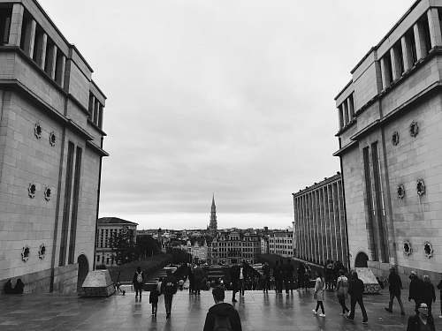 city people walking near buildings grayscale photo black-and-white