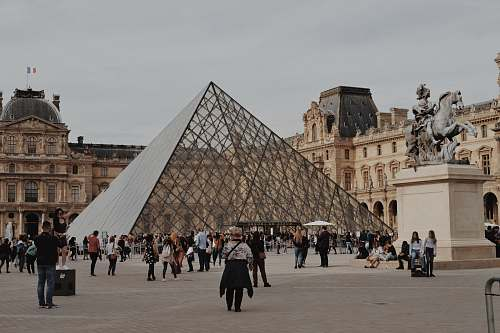 city people walking near Louvre Museum during daytime downtown