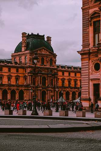 city people walking near Louvre Museum in Paris, France under white skies during daytime downtown