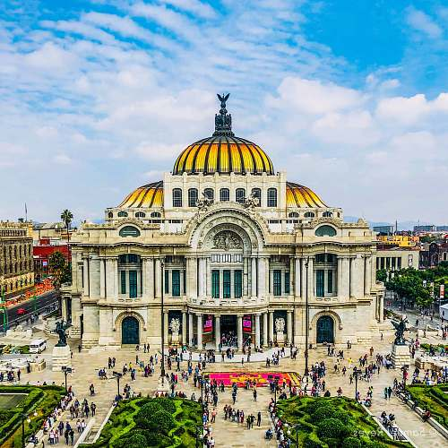 city people walking near Palacio de Bellas Artes in Mexico City under white and blue sky during daytime downtown
