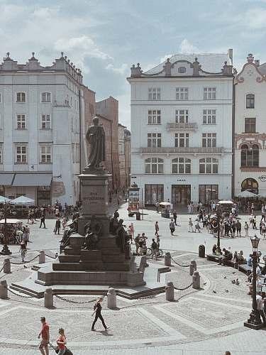 city people walking near statue downtown