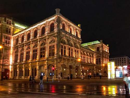 downtown people walking on road near Vienna State Opera during night time city
