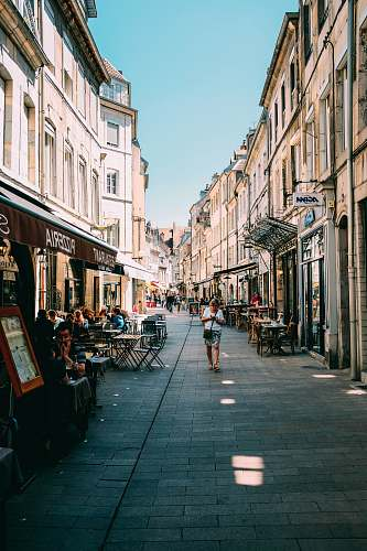 photo human person walking on alleyway with restaurant tables during daytime person free for commercial use images
