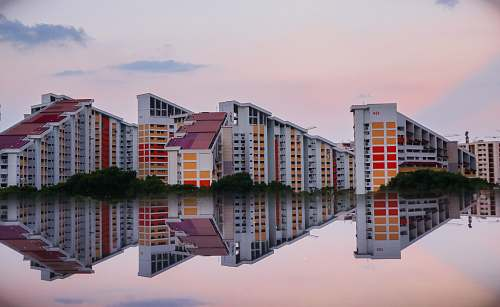 city reflection photography of three buildings high rise