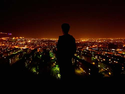 city silhouette photo of person facing on lighted city nature