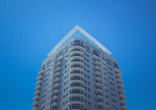 photo condo white and gray concrete building at daytime housing free for commercial use images