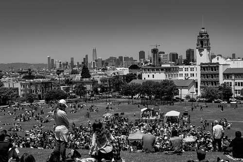 urban grayscale photo of people on field black-and-white