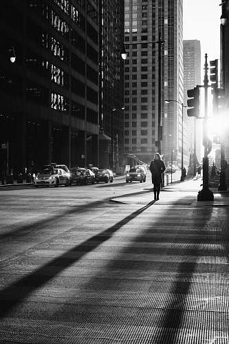 street grayscale photo of woman walking on road black-and-white