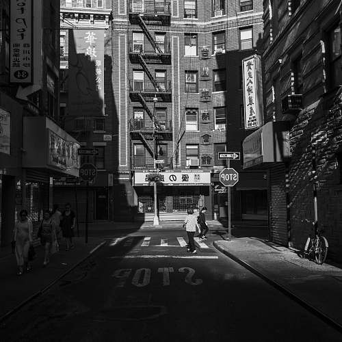 building grayscale photography of two women walking on road during daytime black-and-white