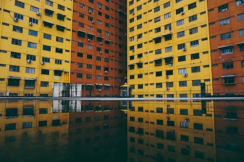 building high-rise building reflection on body of water urban