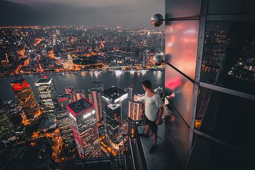 landscape man standing at buildings rooftop overlooking city nature