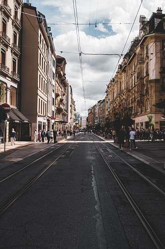 building people walking on side walk beside brown building street