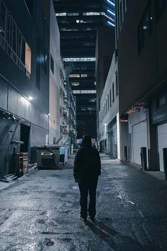 building person in a alley during nighttime with lights road