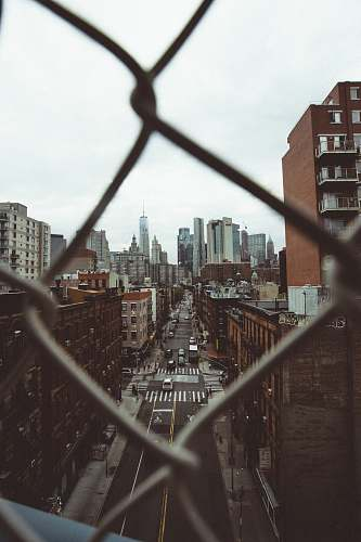 urban photo of city building with cyclone fence frame town