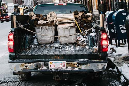 vehicle pickup truck loaded by firewood while parked on concrete roadway boston