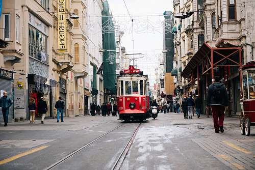 person red tram near between buildings with person walking during daytime people