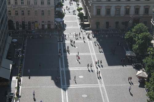 intersection group of people walking on the road surrounded by buildings road
