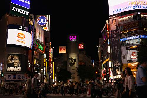 pedestrian crowd of people walking beside buildings during nightime person