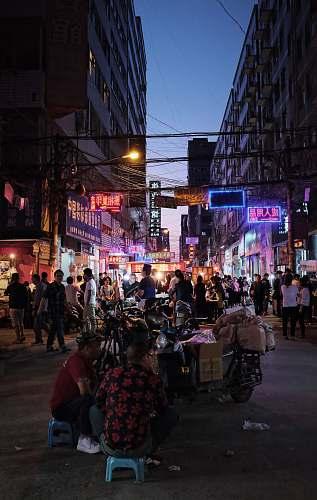 pedestrian people walking on street between buildings person