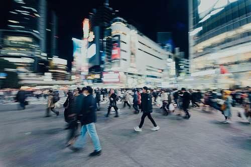 pedestrian people walking on street near buildings during nighttime person