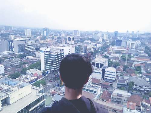 nature man standing at rooftop overlooking city outdoors
