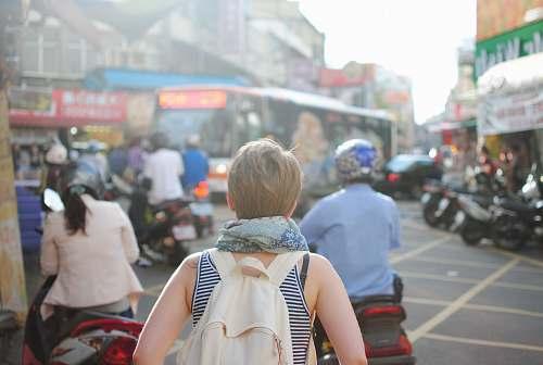 people woman wearing backpack walking on road traffic
