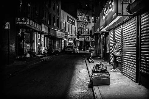 photo road grayscale photography of woman standing infront of store shutter door at night black-and-white free for commercial use images