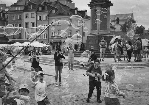 city people and children playing at the streets during day black-and-white