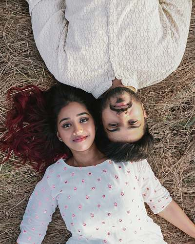clothing high-angle photography of woman and man lying on brown grass sleeve