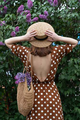 clothing woman in white and black polka dot dress wearing brown straw hat standing near purple flowers hat