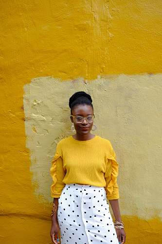 clothing woman in yellow crew neck long sleeve shirt leaning on yellow painted wall baltimore