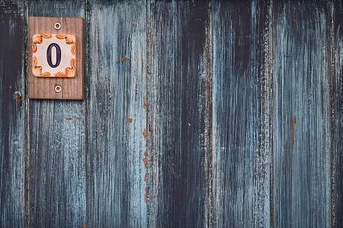 texture A weathered wooden wall with a small plaque with the number zero wood