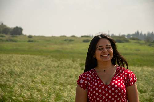 person woman in red and white polka dot shirt standing on green grass field during daytime smile
