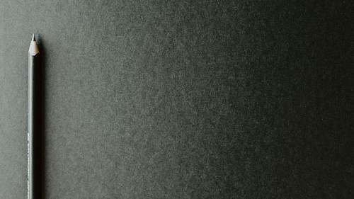grey black pencil on black surface word