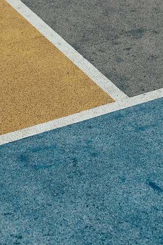 hong kong closeup gray, yellow, and blue painted pavement minimal