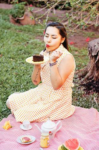 human woman eating cake while sitting on grass field person