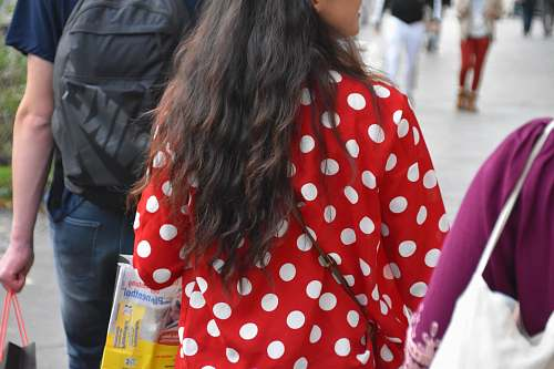person woman in red and white polka dot long sleeve shirt holding plastic bottle human