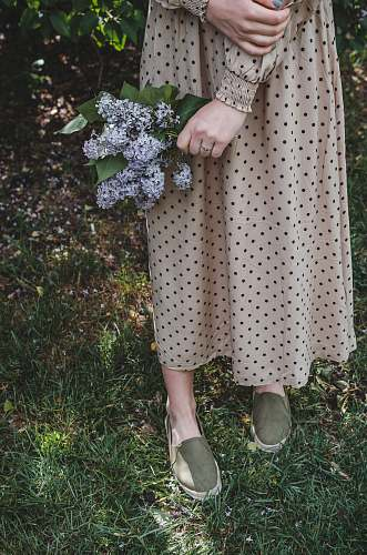 apparel woman in white and black polka dot dress and white shoes standing on green grass field clothing