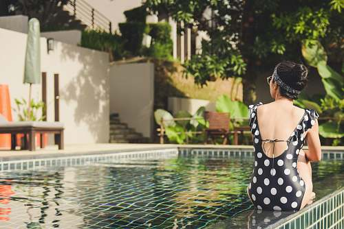 human woman sitting beside pool near house during daytime person