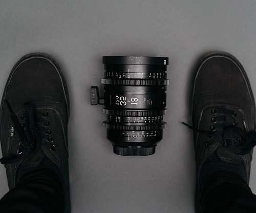 clothing black 18 35 camera zoom lens on floor near person wearing black Vans Authentic sneakers footwear